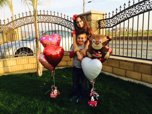 Claidia's Kids holding heart balloons