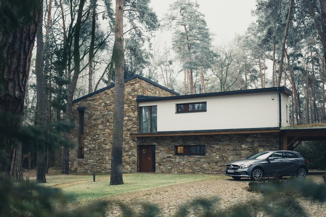 House surrounded with trees with a stone veneer and a car in the driveway.
