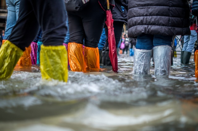 people in boots walking in flood waters