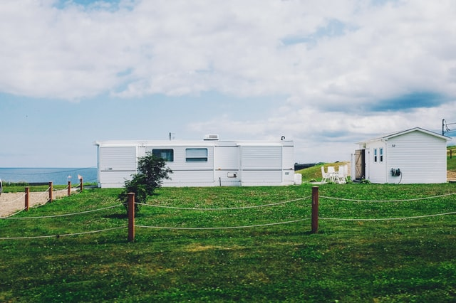 Two mobile homes with a green lawn and next to a beach and ocean