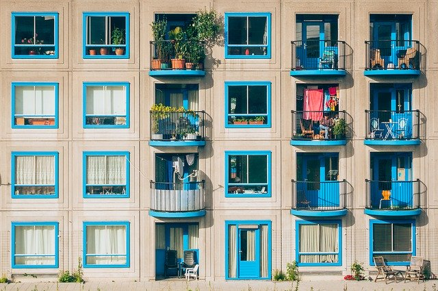 apartment building with balconies and flowers and blue trim around the door and windows.