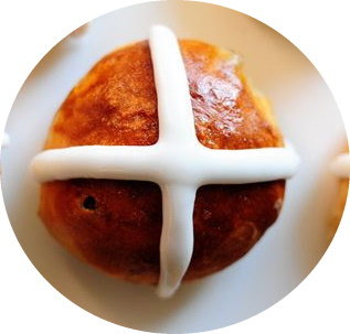 a top down image of a bun with a white icing cross on top